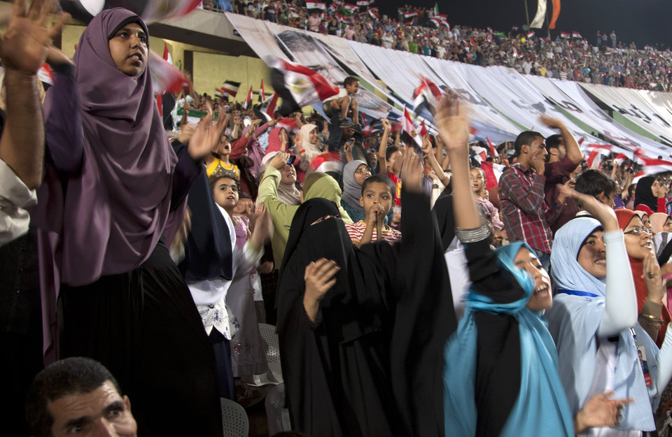 Photo -   Egyptians waves National flags upon the arrival of Egyptian President Mohammed Morsi to give a speech at Cairo International Stadium in Cairo, Egypt, Saturday, Oct. 6, 2012. Egypt's first civilian and Islamist president to take office has marked nearly 100 days in office surrounded by thousands of spectators, most of whom appeared to be supporters of his Muslim Brotherhood party.(AP Photo/Khalil Hamra)