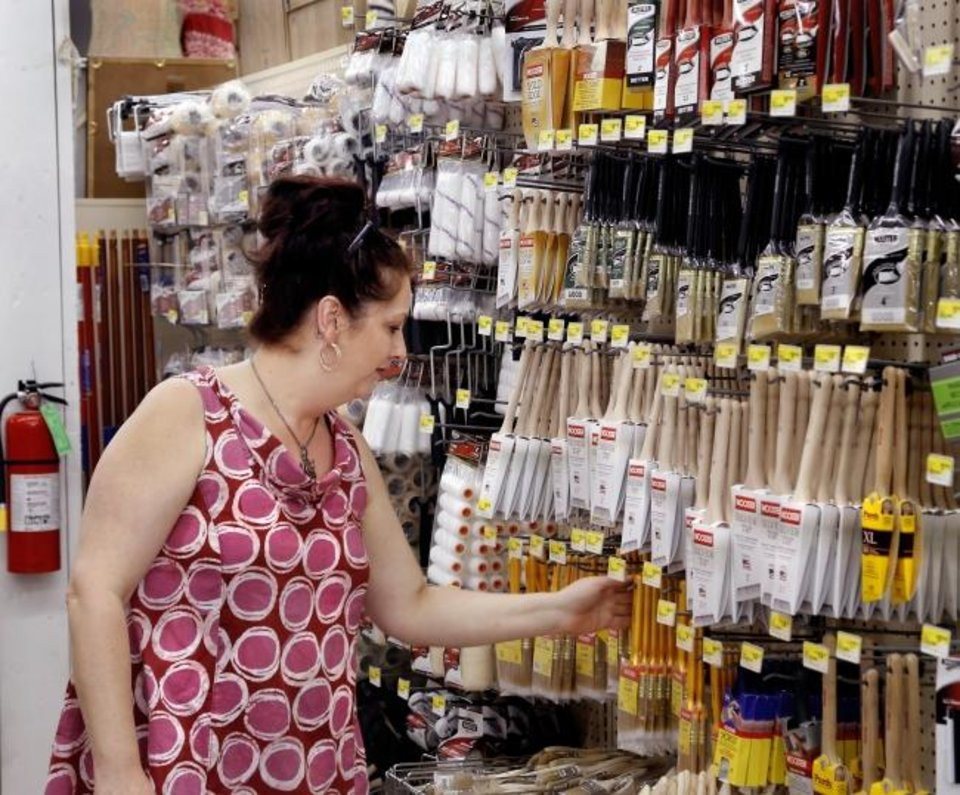 Photo -  Jessica Host works in the paint department at Ross Seed Co. and True Value Hardware Store on Wednesday in El Reno. [Jim Beckel/The Oklahoman]