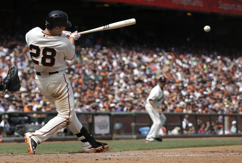 Photo - San Francisco Giants' Buster Posey (28) hits a single to score Angel Pagan during the seventh inning of a baseball game against the Chicago White Sox in San Francisco, Wednesday, Aug. 13, 2014. (AP Photo/Jeff Chiu)