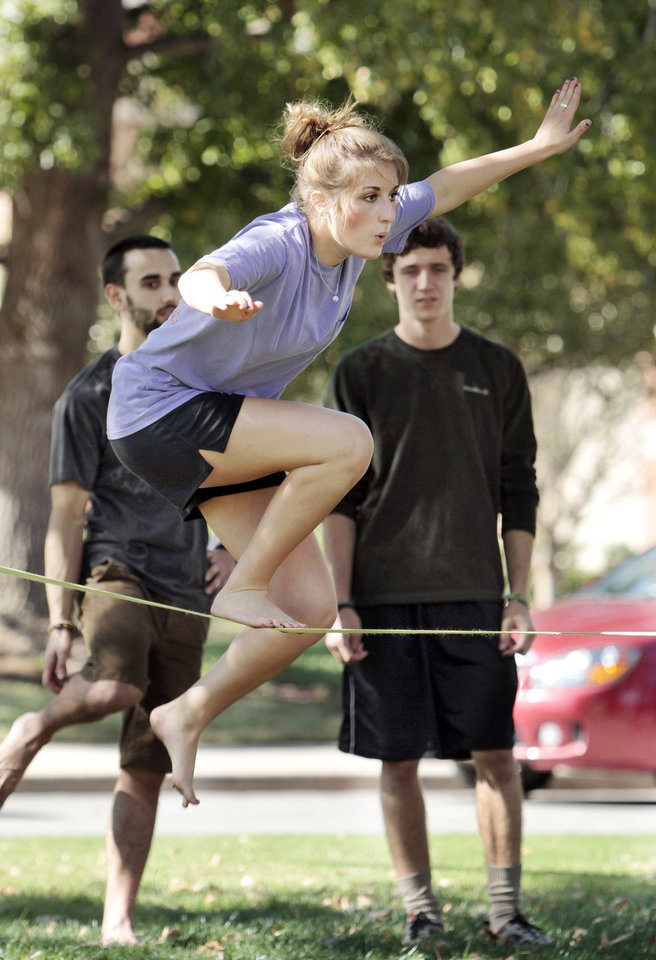 Emily O'Kelley, Tulsa freshman, takes in the sun and a chance to slack line on the campus of the University of Oklahoma (OU) on Tuesday, Oct. 16, 2012 in Norman, Okla.  Behind are Max Munchinski, left, and Adam Stackable.  Photo by Steve Sisney, The Oklahoman