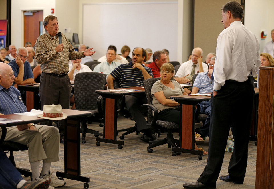 Photo - Steve Byas, of Norman, asks a question to Rep. Tom Cole, R-Moore, during a town hall meeting at Rose State College in Midwest City, Tuesday, September 3, 2013. Photo by Bryan Terry, The Oklahoman  BRYAN TERRY - THE OKLAHOMAN