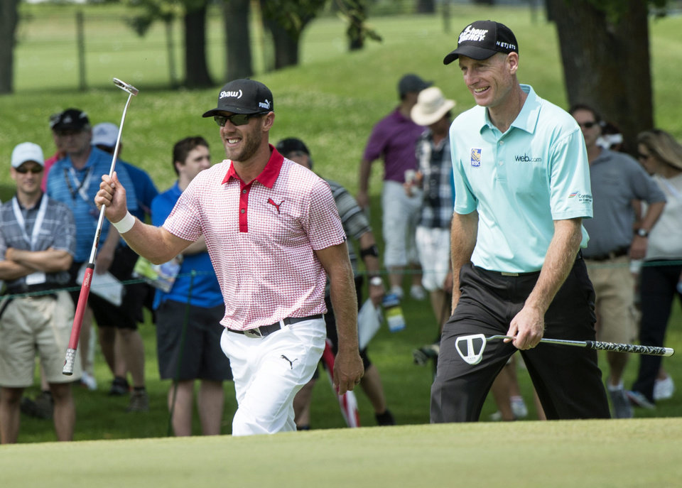 Photo - Graham DeLaet, left, of Canada, walks up the the 9th green with Jim Furyk during second round play at the Canadian Open golf championship Friday, July 25, 2014 in Montreal. (AP Photo/The Canadian Press, Paul Chiasson)