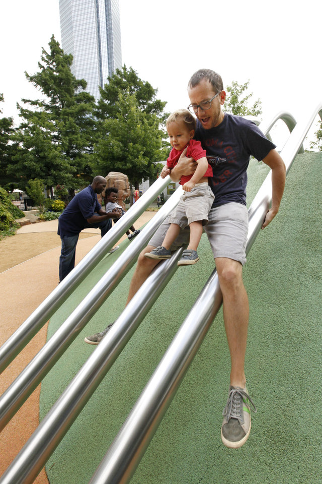 Photo -  Brandon Atkinson slides down poles with his son Griffin, 2, in the children's area at the Myriad Gardens. Photo by Paul Hellstern, The Oklahoman   PAUL HELLSTERN -