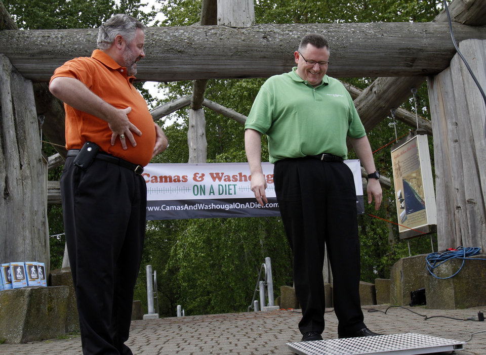 Photo -   Washougal Mayor Sean Guard, left, coaxes Camas Mayor Scott Higgins to step on the scales during their weigh-in in Washougal, Wash., Wednesday, May 2, 2012. The mayors of the two neighboring Washington state towns on the banks of the Columbia River are embarking on a