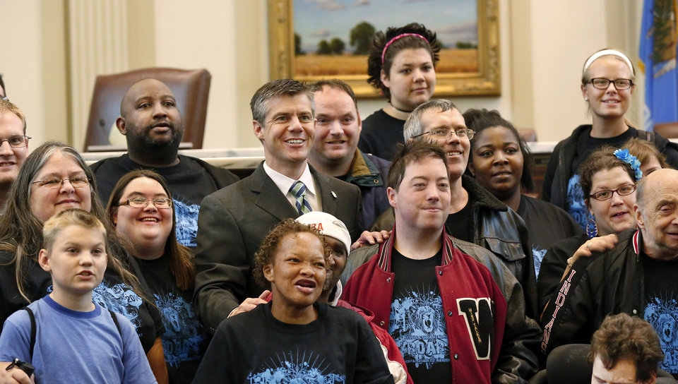 Photo -  Rep. Arthur Hulbert, center, wearing a necktie, poses Thursday on the floor of the House for a photo with constituents from Muskogee. Incor, an agency for developmentally disabled individuals, brought 54 people to the rally.    Jim Beckel -