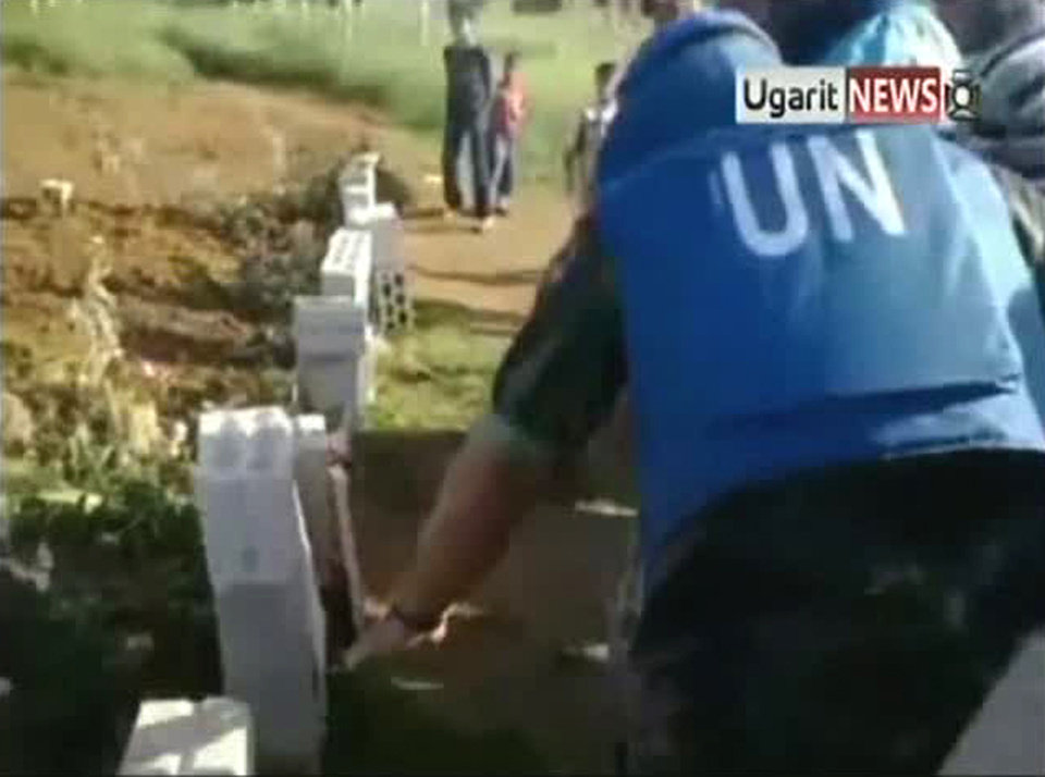 Photo -   In this image made from amateur video released by Ugarit News and accessed Saturday, May 5, 2012, a U.N. observer, right, inspects what residents of the town of Taftanaz, Syria, tell him is a mass grave. The international group Human Rights Watch has said regime soldiers raiding the town on the Turkish border in early April killed 35 detained civilians execution-style and opened fire on others trying to flee. (AP Photo/Ugarit News via AP video) TV OUT, THE ASSOCIATED PRESS CANNOT INDEPENDENTLY VERIFY THE CONTENT, DATE, LOCATION OR AUTHENTICITY OF THIS MATERIAL
