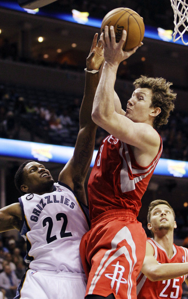 Houston Rockets' Omer Asik, right, of Turkey, grabs a defensive rebound over Memphis Grizzlies' Rudy Gay (22) as Rockets' Chandler Parsons (25) watches during the first half of an NBA basketball game in Memphis, Tenn., Friday, Nov. 9, 2012. (AP Photo/Daniel Johnston)