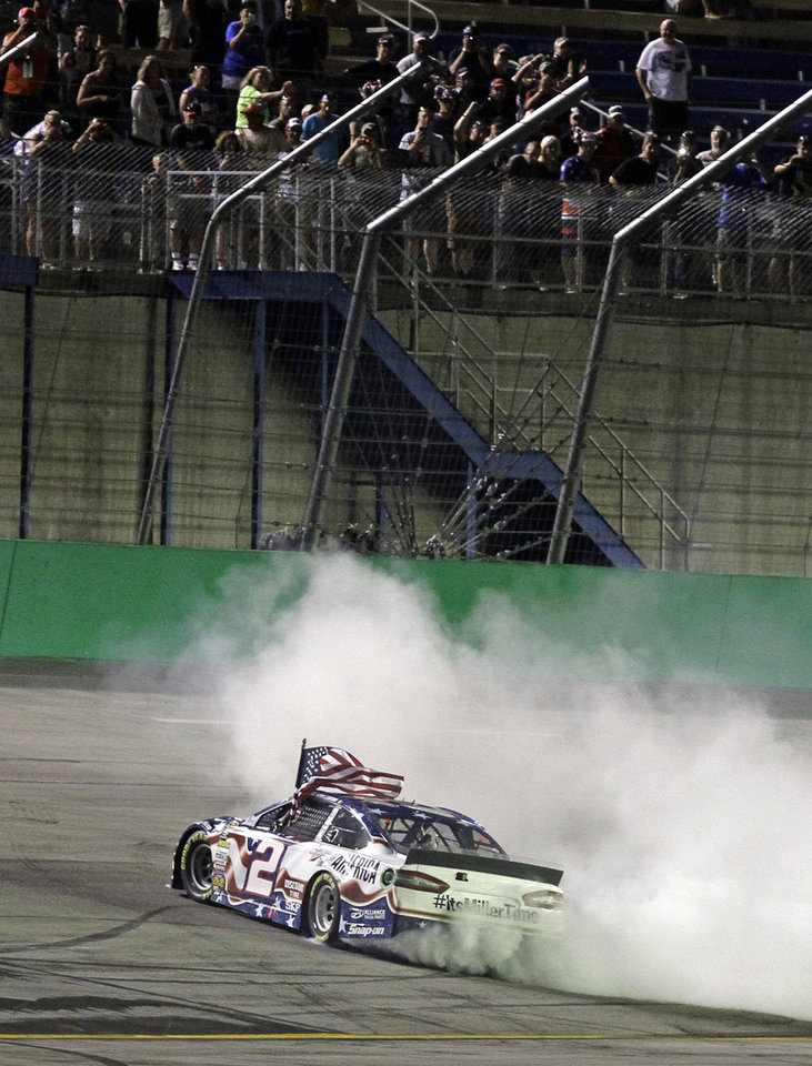 Photo - Brad Keselowski does a burnout after winning the NASCAR Sprint Cup series auto race Saturday, June 28, 2014, at Kentucky Speedway in Sparta, Ky. (AP Photo/Garry Jones)