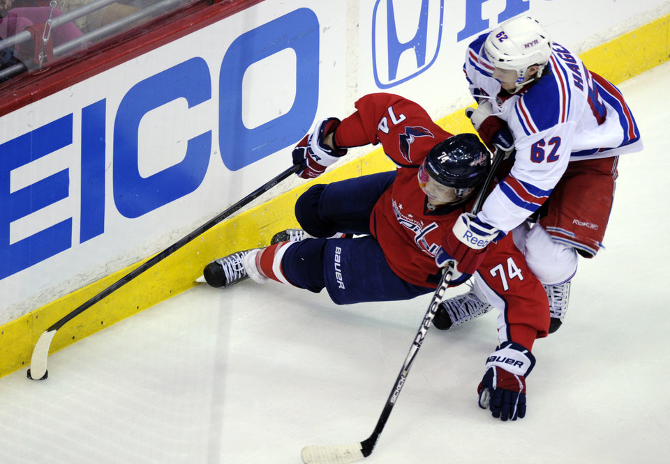 Washington Capitals defenseman John Carlson (74) tries to keep control of the puck under pressure from New York Rangers left wing Carl Hagelin (62) during the second period of Game 3 of their NHL hockey Stanley Cup second-round playoff series at the Verizon Center in Washington, Wednesday, May 2, 2012. (AP Photo/Susan Walsh)
