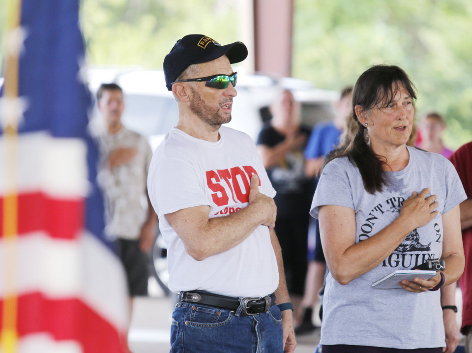 Photo - Steve and Susan Maguire sing along during the National Anthem during the Victimsofiminentdomain.com rally at Choctaw Creek Park, in Choctaw, against the eastern Oklahoma county turnpike leg that the Oklahoma Turnpike Authority has proposed building Friday, August 12, 2016. Photo by Doug Hoke, The Oklahoman
