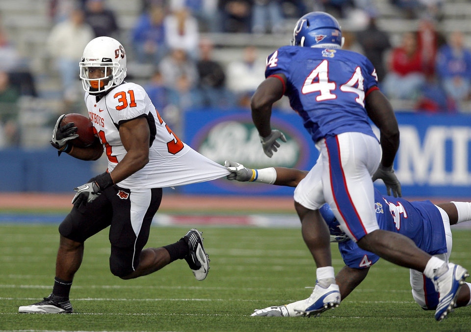 Photo - Oklahoma State's Jeremy Smith (31) slips past Kansas' Prinz Kande (4) and Kansas' Olaitan Oguntodu (44) during the college football game between Oklahoma State (OSU) and Kansas (KU), Saturday, Nov. 20, 2010 at Memorial Stadium in Lawrence, Kan. Photo by Sarah Phipps, The Oklahoman