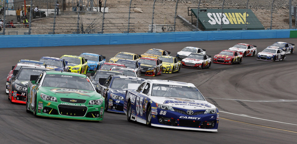 Mark Martin (55) and Kasey Kahne (5) lead the field out of Turn 4 at the start of the NASCAR Sprint Cup Series auto race, Sunday, March 3, 2013, in Avondale, Ariz. (AP Photo/Ross D. Franklin)