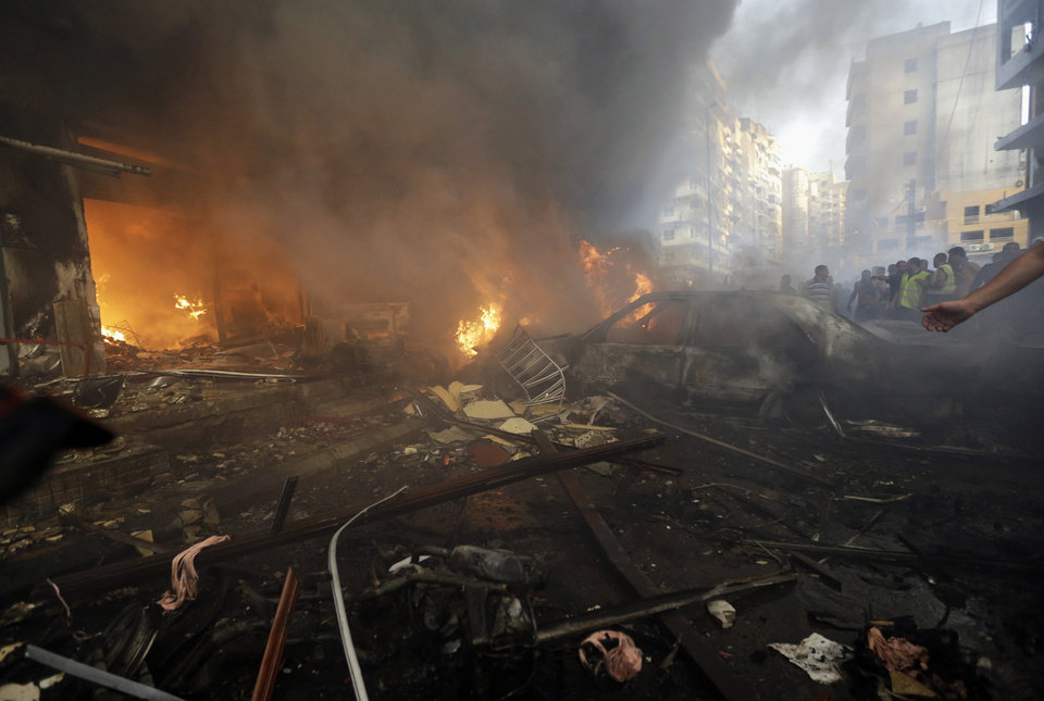 Photo - Burned cars and shops are seen at the site of a car bomb explosion in southern Beirut, Lebanon, Thursday, Aug. 15, 2013. The powerful car bomb ripped through a southern Beirut neighborhood that is a stronghold of the militant group Hezbollah on Thursday, killing people and trapping others in burning buildings, the media said. (AP Photo/Hussein Malla)