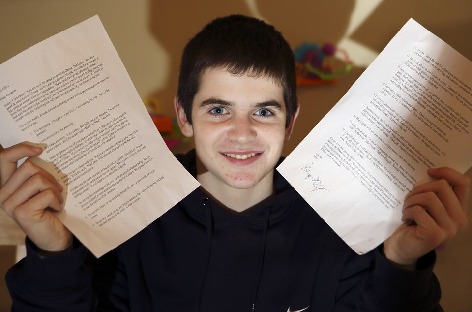 In this Jan. 4, photo, Gregory Hofmann poses with a signed contract at his home in Sandwich, Mass. Hofmann's mother, Janell, drafted the contract which outlines conditions for his use of his first Apple iPhone. (AP Photo/Michael Dwyer) ORG XMIT: MAMD902 <strong>Michael Dwyer - AP</strong>
