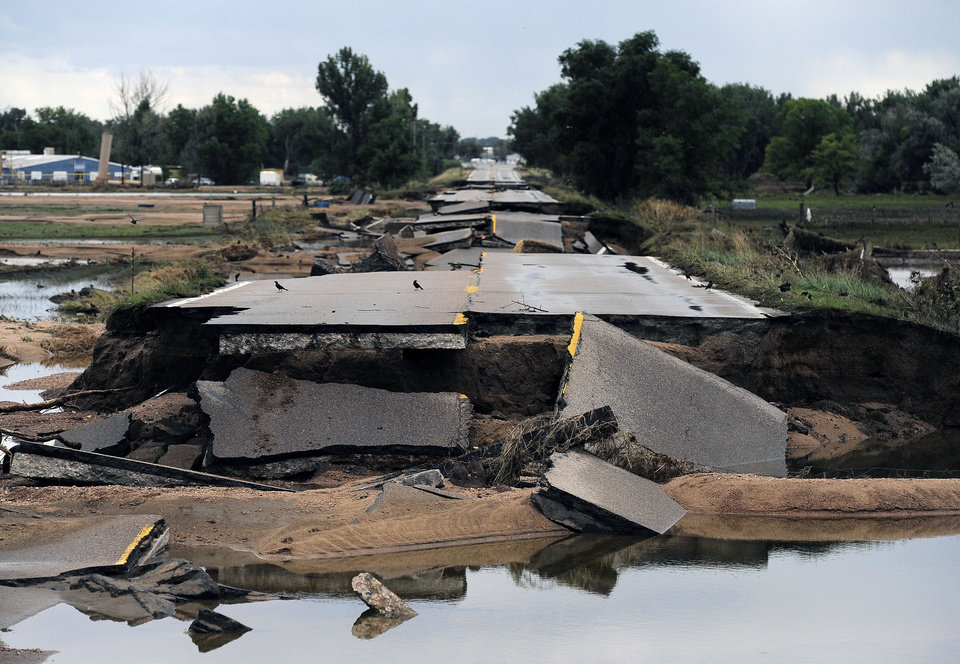 Photo - This photo shows flood damage to Old Highway 34 in Loveland, Colo., on Wednesday, Sept. 18, 2013. As floodwaters recede, cleanup and damage assessment continues after historic flooding. (AP Photo/Chris Schneider)