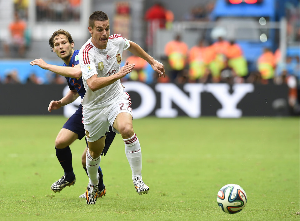 Photo - Spain's Cesar Azpilicueta chases the ball followed by Netherlands' Daley Blind during the group B World Cup soccer match between Spain and the Netherlands at the Arena Ponte Nova in Salvador, Brazil, Friday, June 13, 2014. (AP Photo/Manu Fernandez)