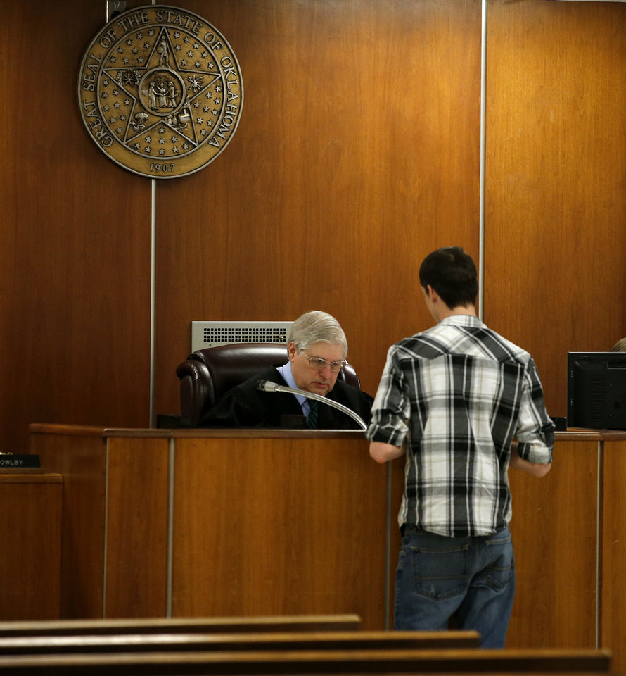 Photo - Kevin Dodd, 19, meets with District Judge Bryan Dixon about getting excused from jury duty in Oklahoma City because he's in school.  Bryan Terry - THE OKLAHOMAN