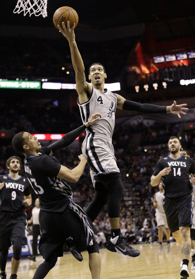 Photo - San Antonio Spurs' Danny Green (4) shoots over Minnesota Timberwolves' Kevin Martin (23) during the first half on an NBA basketball game, Sunday, Jan. 12, 2014, in San Antonio. (AP Photo/Eric Gay)