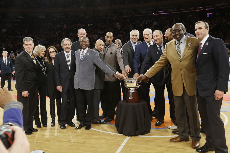 Photo - Phil Jackson, center, Jerry Luckas, center, left, and Bill Bradley, center right, and Earl Monroe, second from right, join other members of the 1972-73 World Champion New York Knicks team as they pose with the Walter Brown Championship trophy during halftime during of an NBA basketball game between the Knicks and the Milwaukee Bucks, Friday, April 5, 2013, in New York. (AP Photo/Frank Franklin II)