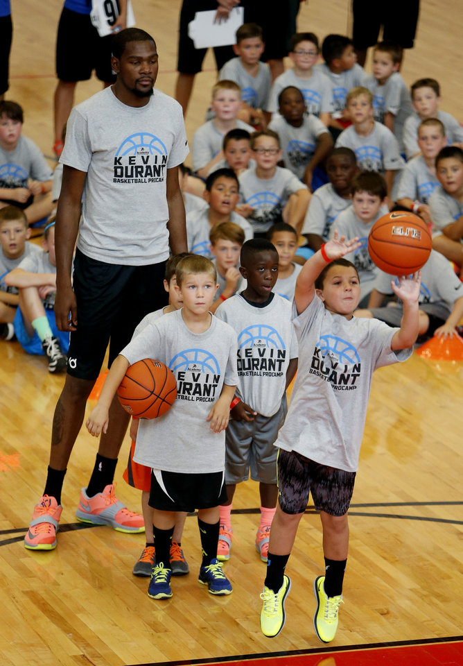 Photo - Kevin Durant engages campers during a shooting contest at his basketball camp on Thursday, Aug. 7, 2014 in Moore, Okla. Photo by Steve Sisney, The Oklahoman