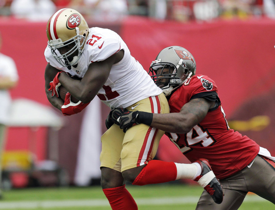 Photo - FILE - In this Dec. 15, 2013, file photo, San Francisco 49ers running back Frank Gore (21) is grabbed by Tampa Bay Buccaneers cornerback Darrelle Revis (24) during the first quarter of an NFL football game in Tampa, Fla. The New England Patriots announced Monday, March 17, 2014, the signing of the three-time All-Pro cornerback Revis. (AP Photo/Chris O'Meara, File)