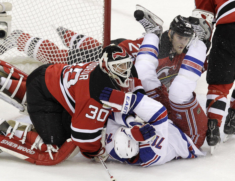 Photo -   New Jersey Devils goalie Martin Brodeur (30) collides with New York Rangers' Mike Rupp center during the first period of Game 4 of an NHL hockey Stanley Cup Eastern Conference final playoff series, Monday, May 21, 2012, in Newark, N.J. Devils' Anton Volchenkov, of Russia, is at rear. (AP Photo/Kathy Willens)