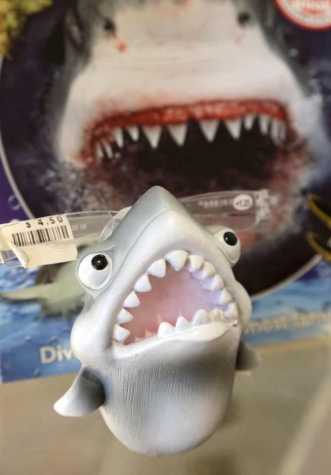 Photo - In this July 2, 2014 photo, an eye glass holder in the shape of a shark rests on a shelf in a souvenir shop in Chatham, Mass. With growing sightings of great white sharks off Cape Cod, local entrepreneurs are feeding the frenzy with their shark-themed memorabilia and apparel. (AP Photo/Steven Senne)
