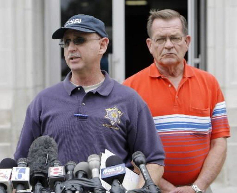 Ben Rosser with the OSBI speaks at a press conference at the Okfuskee County Court House about the murders of Taylor Placker and Skyla Whitaker. In back is Sheriff Jack Choate. Photo by David McDaniel