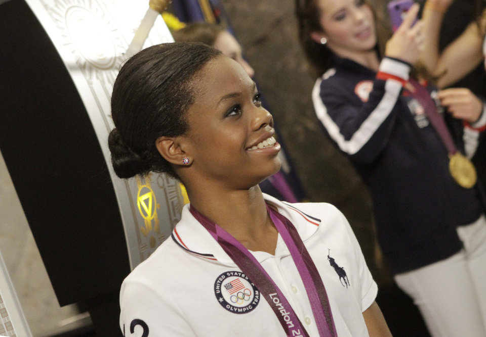 Photo -   U.S. Women's Gymnastics Olympic team gold-medal winner Gabby Douglas poses with team members at the Empire State Building, Tuesday, Aug. 14, 2012 in New York. (AP Photo/Alex Katz)