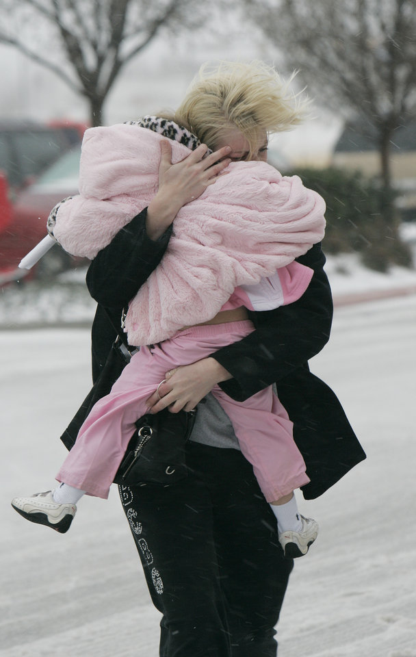 Photo - Julie Nelson shields her daughter Caiden Cauwell, 3, from the weather as she does some last-minute shopping in  Norman Thurs. Dec. 24, 2009. Photo by Jaconna Aguirre, The Oklahoman.