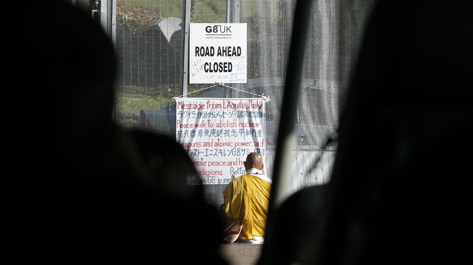 Photo - Anti-nuclear campaigner and Japanese Buddhist Monk Toyoshige Sekiguchi sits with his banner in front of a security gate outside on the G-8 summit at the Lough Erne golf resort in Enniskillen, Northern Ireland on Tuesday, June 18, 2013. The final day of the G-8 summit of wealthy nations is ending with discussions on globe-trotting corporate tax dodgers, a lunch with leaders from Africa, and suspense over whether Russia and Western leaders can avoid diplomatic fireworks over their deadlock on Syria's civil war. (AP Photo/Lefteris Pitarakis)