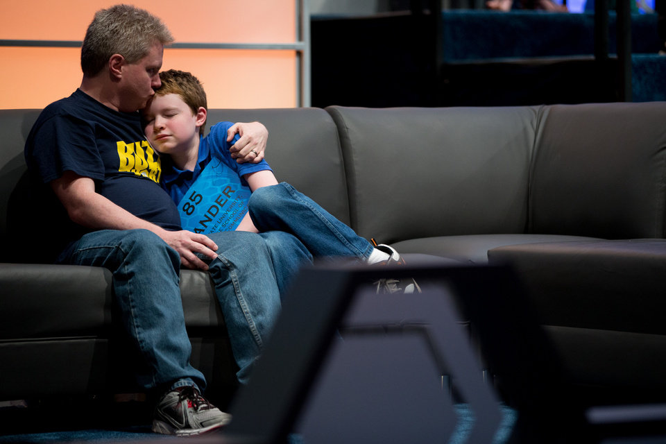Photo - Zander Reed, 12, of Ames, Iowa, gets a kiss from his father, Todd, after incorrectly spelling his word during the 2015 Scripps National Spelling Bee, Wednesday, May 27, 2015, in Oxon Hill, Md. (AP Photo/Andrew Harnik)