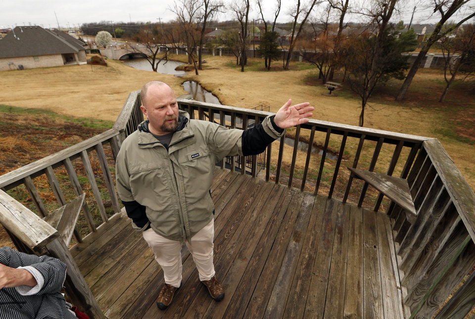 Photo -  Jeff Puckett, president of the Summit Lakes Homeowners Association, talks about a problem with the community's dam, which is seeping and has been placed on the