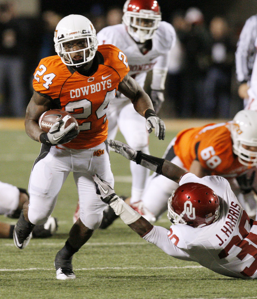 Photo - OSU's Kendall Hunter (24) carries the ball in the fourth quarter past Javon Harris (24) of OU during the Bedlam college football game between the University of Oklahoma Sooners (OU) and the Oklahoma State University Cowboys (OSU) at Boone Pickens Stadium in Stillwater, Okla., Saturday, Nov. 27, 2010. OU won, 47-41. Photo by Nate Billings, The Oklahoman