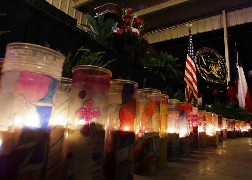 Photo - Candles burn at the front of a stage during a memorial service, Thursday, April 17, 2014, in West, Texas. Thousands gathered for the service that honored all those killed in a fertilizer plant explosion one year ago. (AP Photo/Tony Gutierrez)