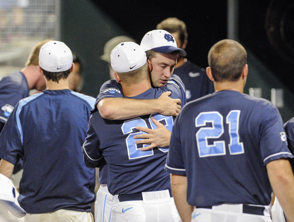 North Carolina's Hobbs Johnson (29) and Chris Munnelly, center facing the camera, console each other after losing 4-1 to UCLA in an NCAA College World Series baseball game in Omaha, Neb., Friday, June 21, 2013. (AP Photo/Eric Francis)