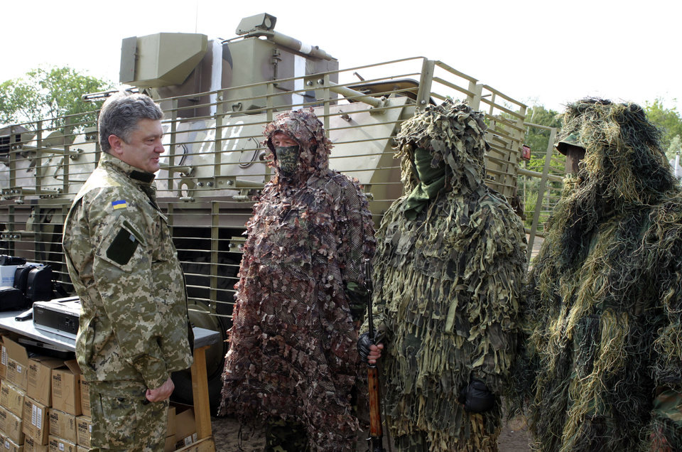 Photo - In this photo taken on Friday, June  20, 2014  in Izyum close to Slovyansk, eastern Ukraine Ukrainian President Petro Poroshenko, left, visits troops. Poroshenko in a televised address early Tuesday, July 1, 2014, said he was abandoning a unilateral cease-fire in the conflict with pro-Russian separatists and sending military forces back on the offensive after talks with Russia and European leaders failed to start a broader peace process. The cease-fire expired Monday evening. (AP Photo/Mykhailo Markiv, Pool)