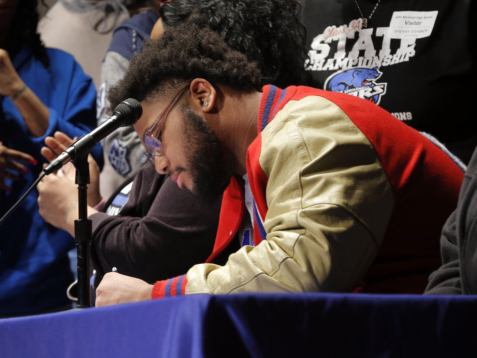 Photo - Nigel Brannon signs to play football at Memphis during an assembly for National Signing Day at John Marshall High School in Oklahoma City, Wednesday, Feb. 7, 2018. Photo by Nate Billings, The Oklahoman