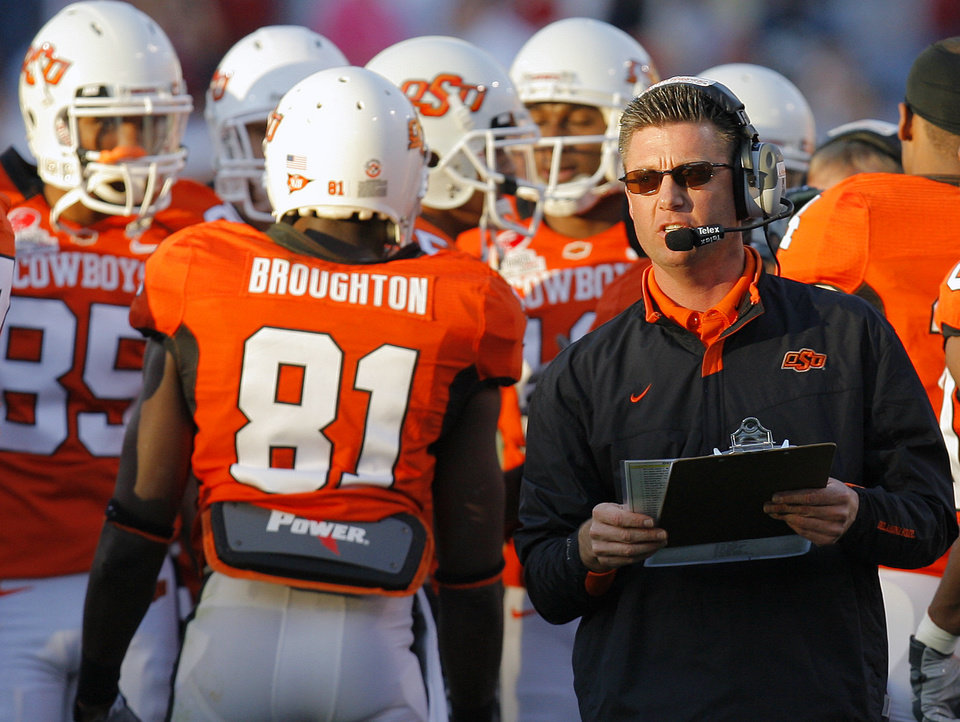 Photo - Oklahoma State coach Mike Gundy leads his team against Indiana in the first half during the Insight Bowl college football game between Oklahoma State University (OSU) and the Indiana University Hoosiers (IU) at Sun Devil Stadium on Monday, Dec. 31, 2007, in Tempe, Ariz. 