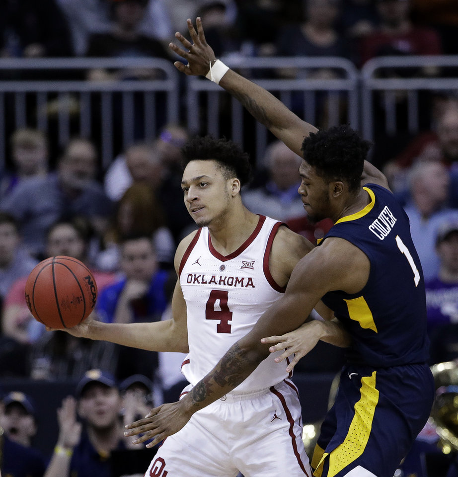 Photo - Oklahoma's Jamuni McNeace (4) looks to pass under pressure from West Virginia's Derek Culver (1) during the first half of an NCAA college basketball game in the Big 12 men's tournament Wednesday, March 13, 2019, in Kansas City, Mo. (AP Photo/Charlie Riedel)