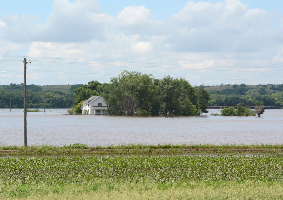 Photo - A farm house sits surrounded by flood water, Thursday, June 19, 2014, in Hawarden, Iowa. Cities in Iowa, Nebraska, and South Dakota are fighting a surging Big Sioux River after heavy rain this week pushed the waterway to record levels in some locations. (AP Photo/Dirk Lammers)