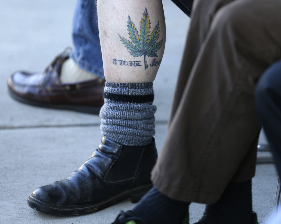 Photo - A man waiting in line to buy recreational marijuana displays his pot-leaf tattoo oustside of Top Shelf Cannabis, Tuesday, July 8, 2014, in Bellingham, Wash., on the first day of legal sales in the state.  (AP Photo/Ted S. Warren)