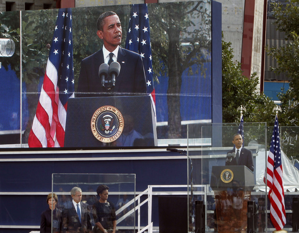 President Barack Obama, far right, speaks as, from left, former First Lady Laura Bush, former President George W. Bush and First Lady Michelle Obama look on as friends and relatives of the victims of 9/11 gather for a ceremony marking the 10th anniversary of the attacks at the National September 11 Memorial at the World Trade Center site, Sunday, Sept. 11, 2011, in New York. (AP Photo/Jason DeCrow)