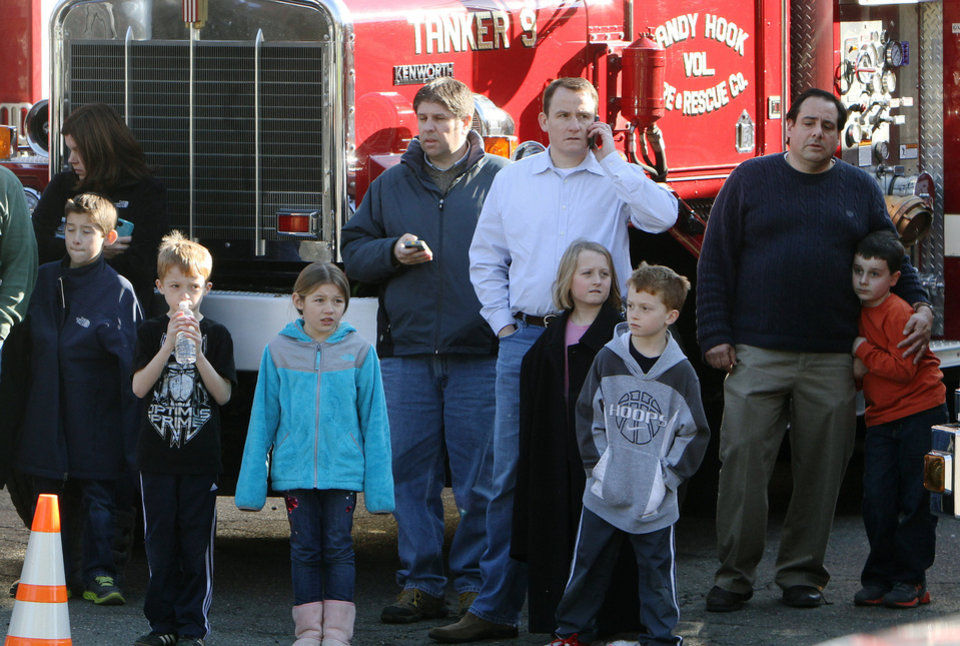 School children wait for their parents at the Sandy Hook firehouse following a mass shooting at the Sandy Hook Elementary School in Newtown, Conn. on Friday, Dec. 14, 2012. (AP Photo/The Journal News, Frank Becerra Jr.) NYC OUT, NO SALES, TV OUT, NEWSDAY OUT; MAGS OUT; MANDATORY CREDIT: THE JOURNAL NEWS, FRANK BECERRA JR.