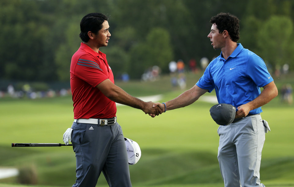 Photo - Jason Day, of Australia, left, and Rory McIlroy, of Northern Ireland, shake hands on the 18th green following the third round of the PGA Championship golf tournament at Valhalla Golf Club on Saturday, Aug. 9, 2014, in Louisville, Ky. (AP Photo/Jeff Roberson)