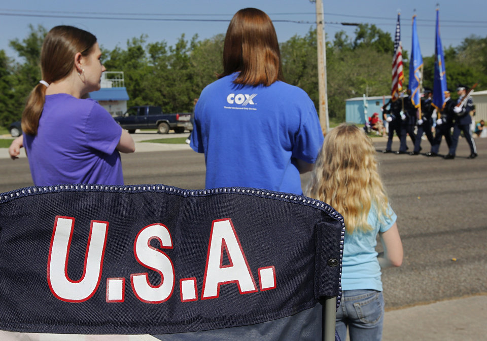 Photo - Lee Ann Kirkland holds her 6-month-old son, Hunter, left, as they and Traci Oswald, center, and daughter, Jade, 6, rise from their chairs as a military color guard passes during the Armed Forces Day parade in Del City. Photo  by Jim Beckel, The Oklahoman.  Jim Beckel - THE OKLAHOMAN