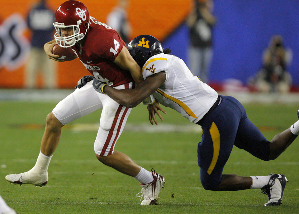 Photo - Oklahoma's Sam Bradford (14) is brought down by West Virginia's Mortty Ivy (44) during the first half of the Fiesta Bowl college football game between the University of Oklahoma Sooners (OU) and the West Virginia University Mountaineers (WVU) at The University of Phoenix Stadium on Wednesday, Jan. 2, 2008, in Glendale, Ariz. 