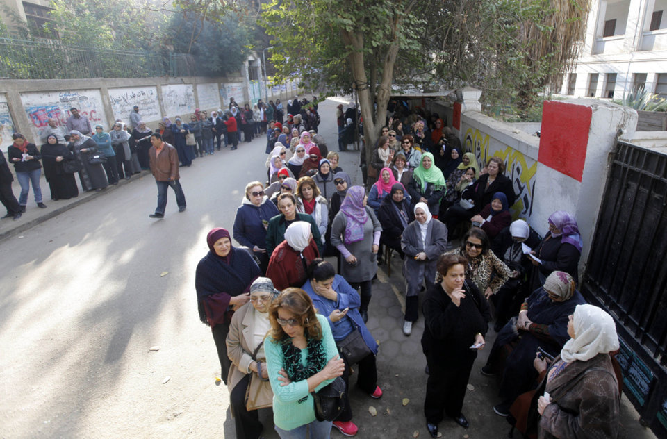 Photo - Egyptian voters line up outside a polling station in Cairo, Egypt, Tuesday, Jan. 14, 2014. Egyptians are voting on a draft for their country's new constitution that represents a key milestone in a military-backed roadmap put in place after President Mohammed Morsi was overthrown in a popularly backed coup last July. (AP Photo/Amr Nabil)