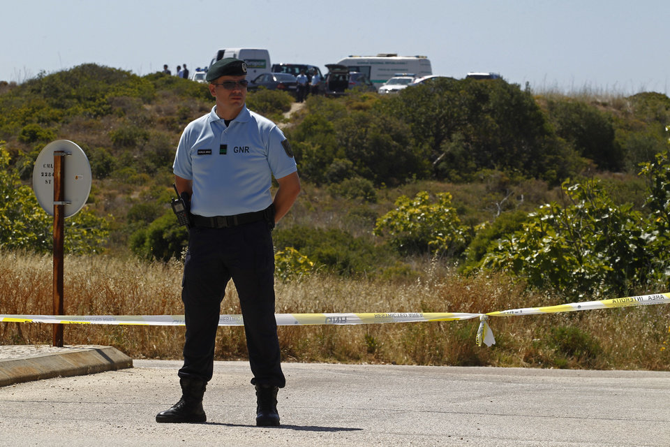 Photo - A Portuguese Republican Guard policeman stands guard by a cordoned-off area with other officers, background, in Praia da Luz, Lagos, southern Portugal, Monday, June 2, 2014. Police investigating the disappearance of Madeleine McCann cordoned off Monday an area of scrubland near where the British girl vanished seven years ago. Officers placed yellow-and-white police tape around the waste ground, which is mostly level and slightly larger than a soccer field, and were expected to conduct a forensic examination of the area in the coming days. (AP Photo/Francisco Seco)