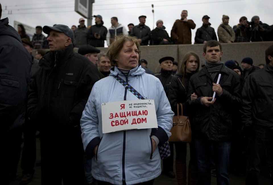"A woman with a placard reading ""I'm not a fascist, I'm not a nationalist, I defend my home!"" watches ultra nationalist demonstrators and activists march to mark National Unity Day, in Moscow, Sunday, Nov. 4, 2012. Chanting ""Russia for Russians"" and ""Migrants today, occupiers tomorrow,"" about 6,000 people, mostly young men, marched through a working-class neighborhood on the outskirts of the capital, while police stood shoulder to shoulder along streets blocked to traffic. (AP Photo/Ivan Sekretarev)"